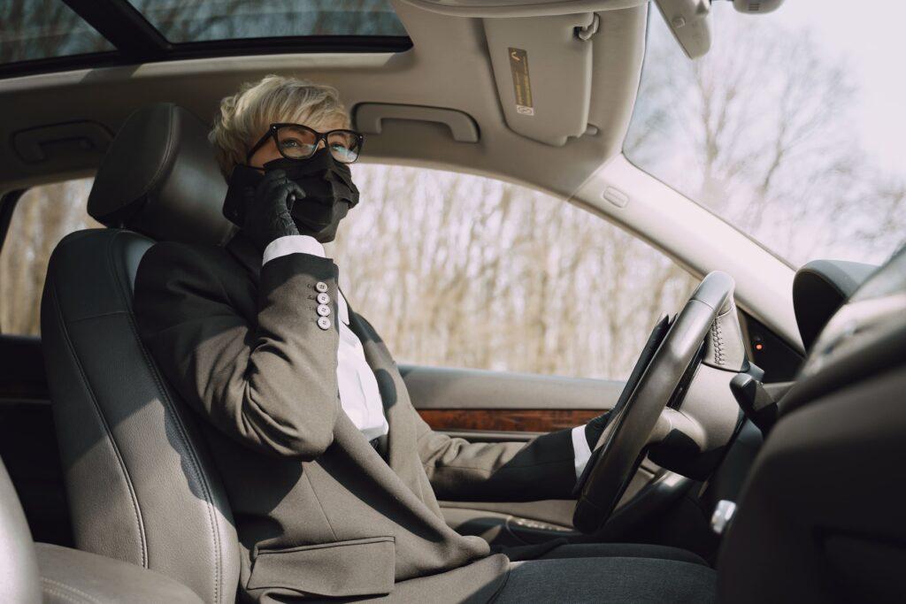 businesswoman in a black mask sitting inside a car 3SH4FNJ min 1 30